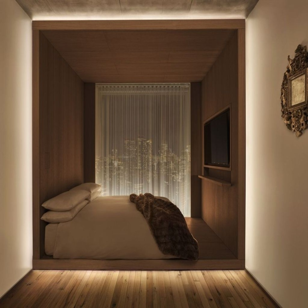 Linear LED lights edge lighting the sleeping are of a modern hotel bedroom. Boca Flasher