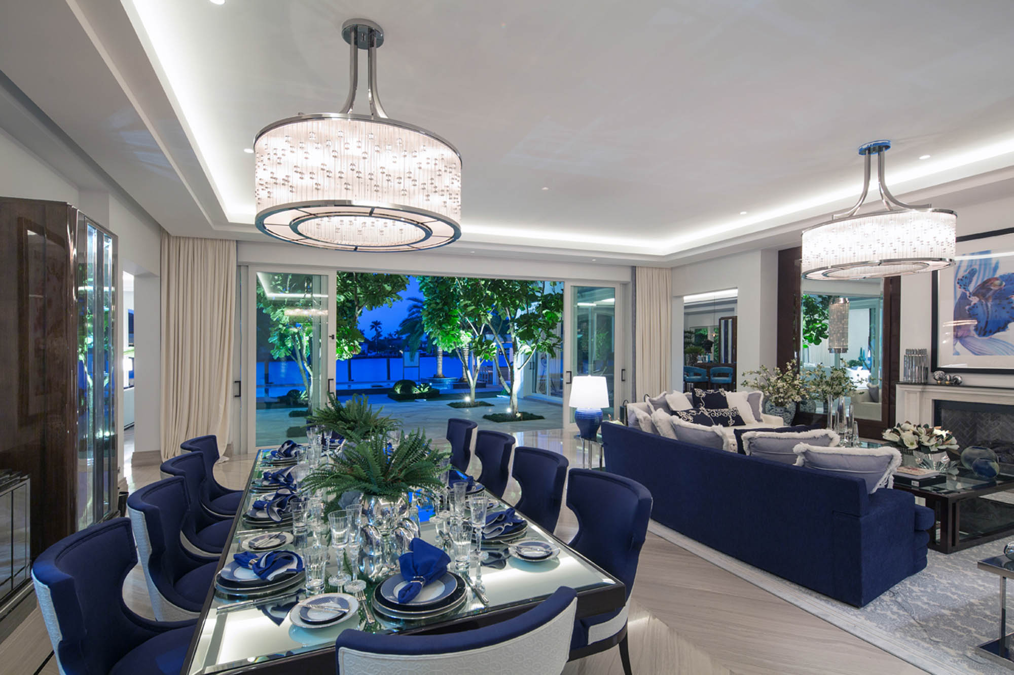 A residential living room lit with LED linear strip cove lighting and large drumb chandeliers, open to an outdoor courtyard at dusk. Boca Fisher