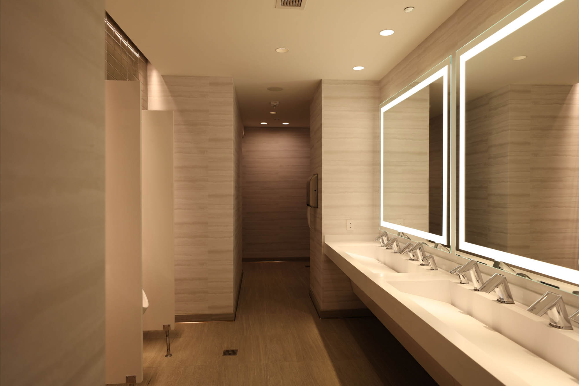 Linear LED strip lights illuminating the edges of large mirrors in the vanity area of a modern hotel public restroom. Boca Flasher